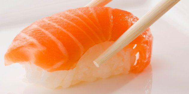 Close-up of Nigiri sushi with salmon held between
