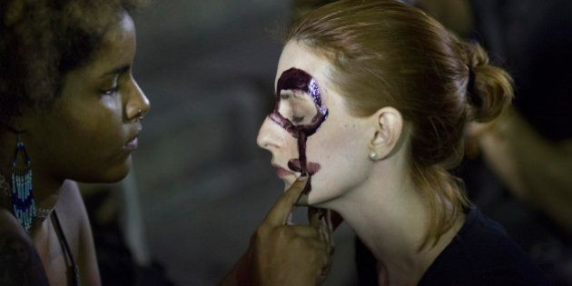 Women paint their faces with female gender symbols for a protest against the gang rape of a 16-year-old...