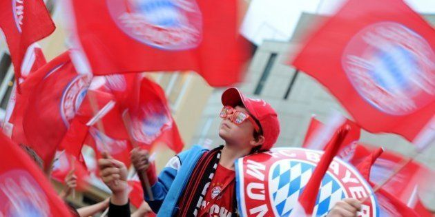 A young fan of Bayern Munich celebrates at the Marienplatz square the team's German football league champion's...