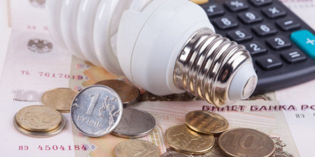 Energy saving concept. Electric light bulb with dollar bills, pen and