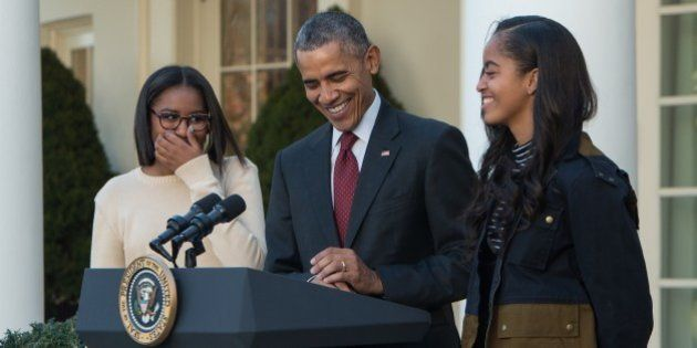 US President Barack Obama laughs with daughters Malia (R) and Sasha before 'pardoning' the National Thanksgiving...