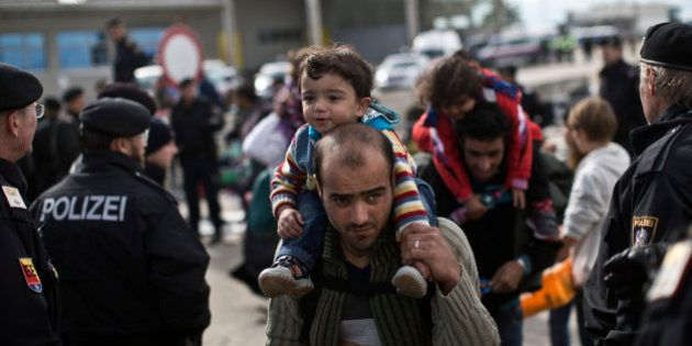 A man carries a child as he waits in line to board a bus organized by the Austrian government in Hegyeshalom,...