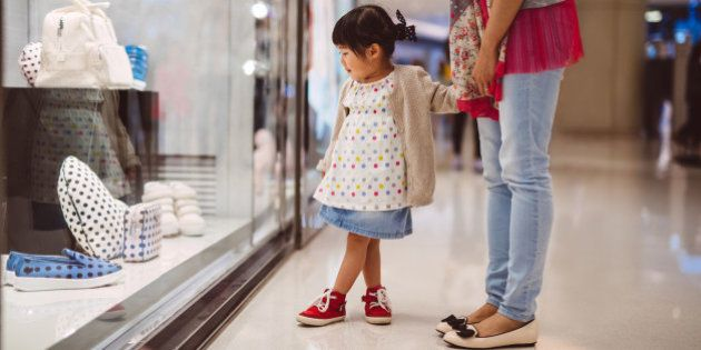 Lovely little girl holding hands with her mom while looking at the shopping window display in the shopping...