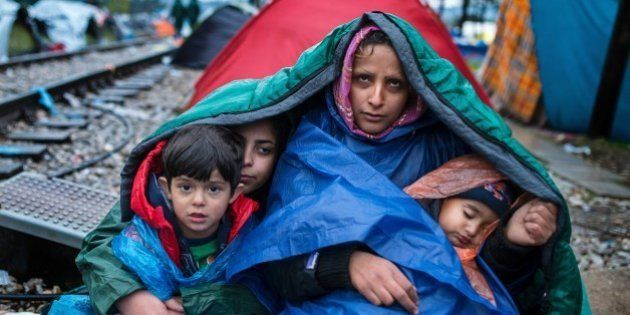 A woman and her children look on as migrants and refugees wait to cross the Greece-Macedonia border in...