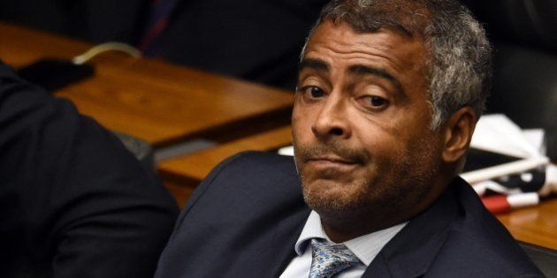 Brazilian senator and former football star Romario follows the voting as lawmakers decide on whether...