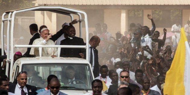 Pope Francis (C) waves as he visits the Koudoukou school, to meet people from the muslim community, after...