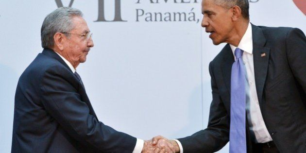 US President Barack Obama (R) shakes hands with Cuba's President Raul Castro during a meeting on the...