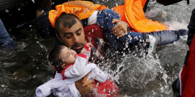 A Syrian refugee holds onto his children as he struggles to walk off a dinghy on the Greek island of...