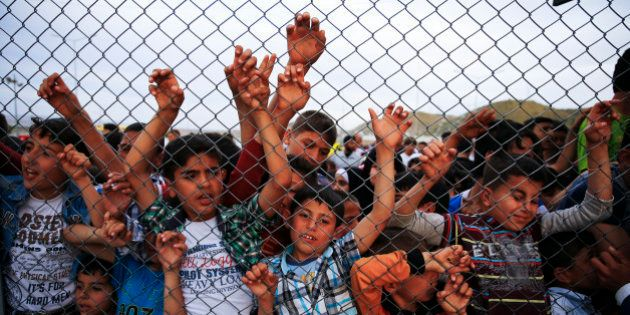 Refugee youths gesture from behind a fence as German Chancellor Angela Merkel, Turkish Prime Minister...