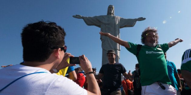 RIO DE JANEIRO, BRAZIL - JUNE 09: Tourists pose for photos in front Christ the Redeemer statue prior...