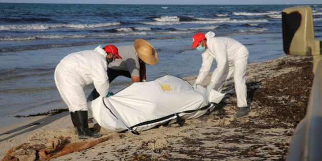 Libyan Red Crescent workers put bodies into body bags, after migrants who died when a boat sank off the...