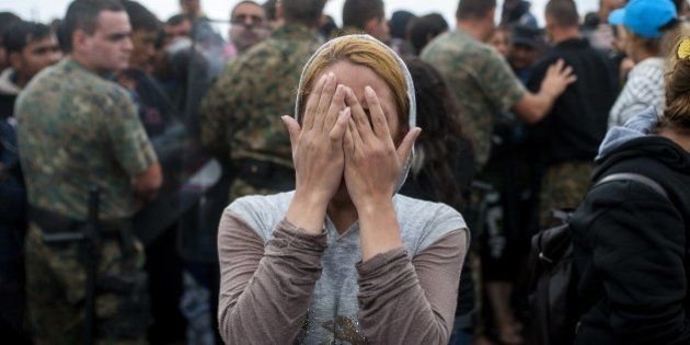 A woman coveres her eyes as migrants and refugees try to break through the Macedonian police cordon,...