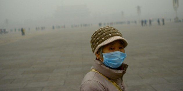 An elderly woman wearing a mask looks on as she visits Tiananmen Square during heavy pollution in Beijing...