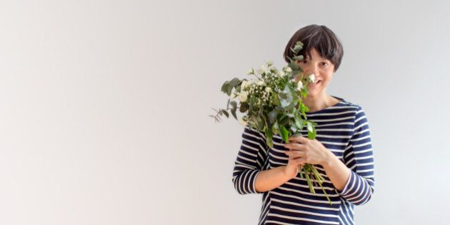 Woman peaking behind bouquet of white roses