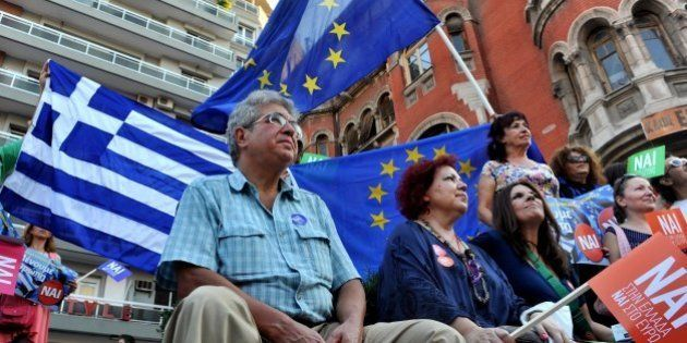 Pro-European Union protesters hold EU and Greek flags and placards reading ''yes'' during a demonstration...