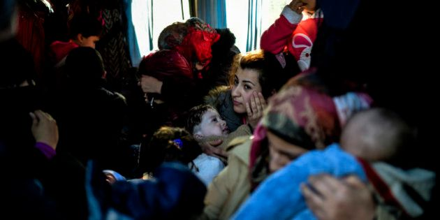 A woman holds child in a van after being detained by Turkish soldiers with other Syrians trying to reach...
