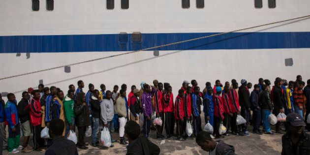 LAMPEDUSA, ITALY - APRIL 23: Migrant men wait in line to board a ship bound for Sicily on April 23, 2015...