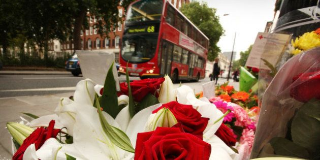 LONDON, ENGLAND - JULY 07: A bus passes floral tributes placed next to a memorial remembering the victims...