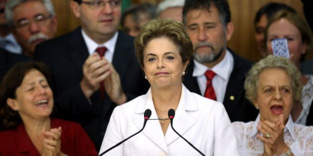 Supporters applaud as suspended Brazilian President Dilma Rousseff (C) addresses the audience after the...