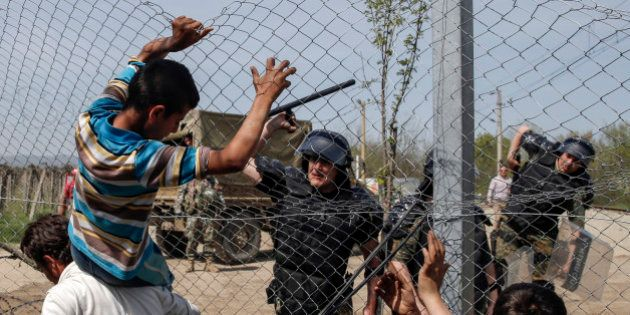 A Macedonian policeman uses his baton to prevent migrants and refugees to open the border fence at a...
