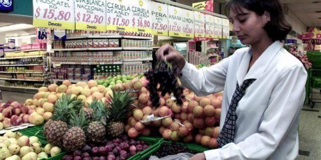 MONTEVIDEO, URUGUAY: An supermarket employee in Montevideo, Uruguay, choses grapes 22 March 2001. The...