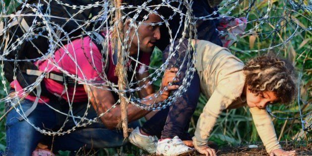 A young girl of a migrant's family is helped by her father as they creep under a barbed fence near the...