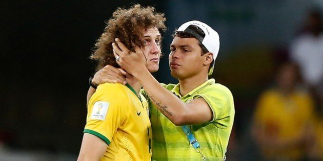 Brazil's defender Thiago Silva (R) conforts Brazil's defender David Luiz after the semi-final football...