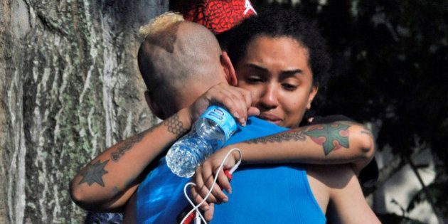 Friends and family members embrace outside the Orlando Police Headquarters during the investigation of...