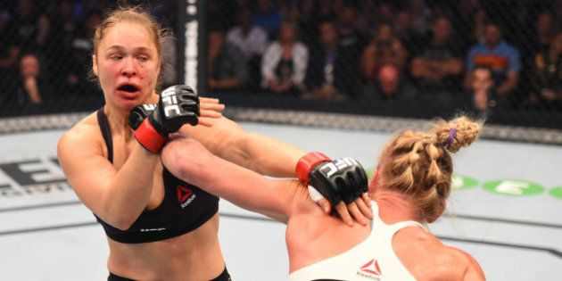 MELBOURNE, AUSTRALIA - NOVEMBER 15: (R-L) Holly Holm of the United States punches Ronda Rousey of the...