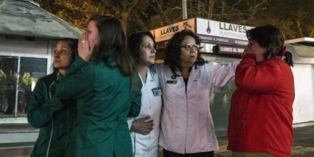 Women remain at a street during a strong quake in Santiago on September 16, 2015. A strong 7.2-magnitude...