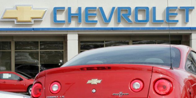 The company sign hangs over the tail of an unsold 2007 Cobalt coupe at a Chevrolet dealership in the...
