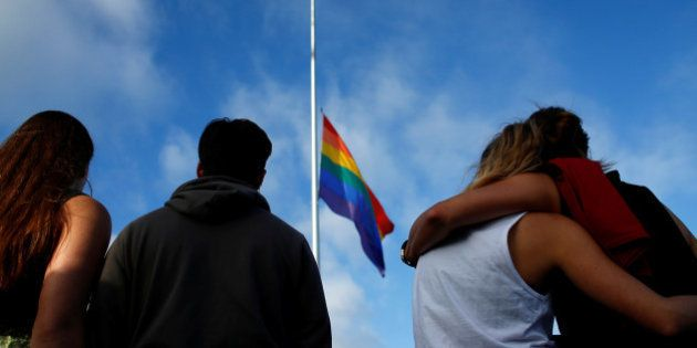 Mourners gather under a LGBT pride flag flying at half-mast for a candlelight vigil in remembrance for...