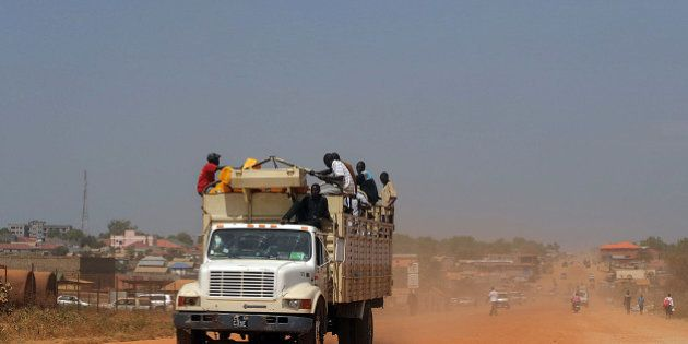 South Sudanese sit on a truck with their belongings as it heads out of Juba on December 21, 2013 where...