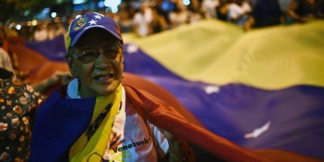 A Venezuelan opposition supporter celebrates the results of the legislative election in Caracas, on December...