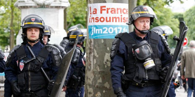 French CRS riot police stand on the route taken by striking employees during a demonstration in Paris...