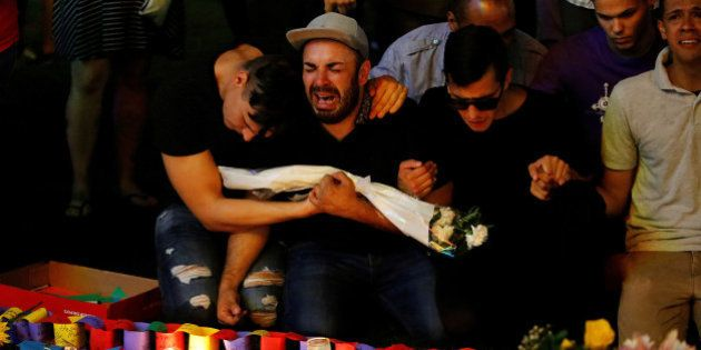 A man sits and cries after taking part in a candlelight memorial service the day after a mass shooting...
