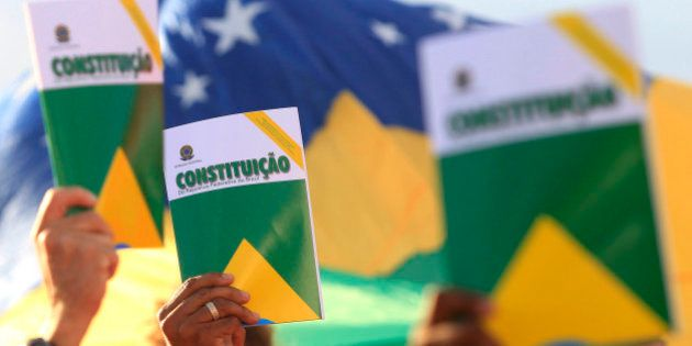 Activists hold the Brazilian constitution during a demonstration in support of the Workers' Party (PT)...