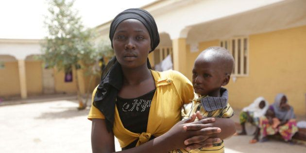 Binta Ibrahim, holds an unidentified child after she described how she trekked for two days from Nbitha...