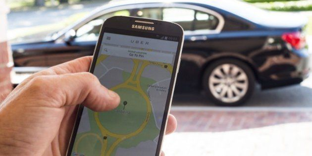 CANBERRA, AUSTRALIA - OCTOBER 30: A person uses the UberX app on October 30, 2015 in Canberra, Australia....