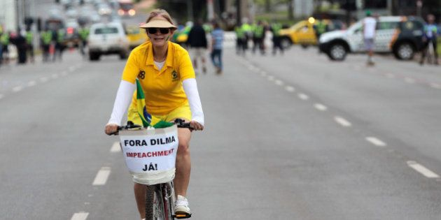 A demonstrator arrives by bike with a placard written in