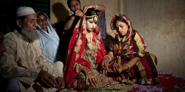 MANIKGANJ, BANGLADESH - AUGUST 20: 15 year old Nasoin Akhter sits with relatives while posing for photos...