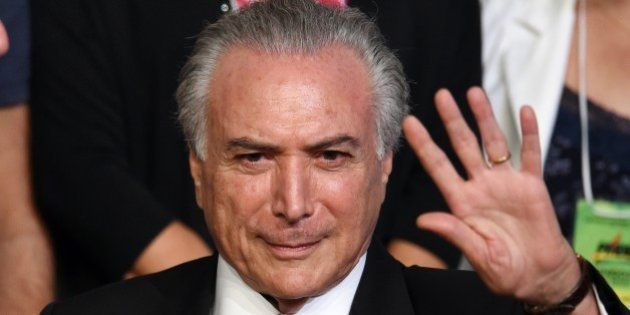 Brazilian Vice President Michel Temer waves during the Brazilian Democratic Movement Party (PMDB) national...