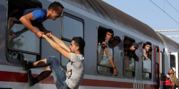 Migrants board through a window a train heading to Zagreb at a railway station, near the official border...