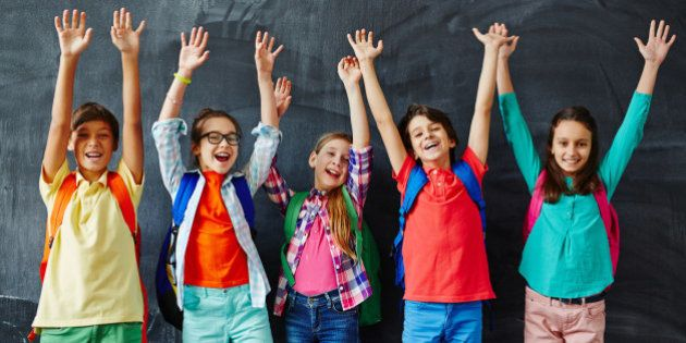 Ecstatic kids raising hands while standing by