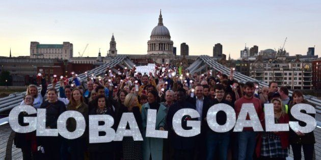 Activists stand on the Millennium bridge in London to demand action on poverty, inequality and climate...