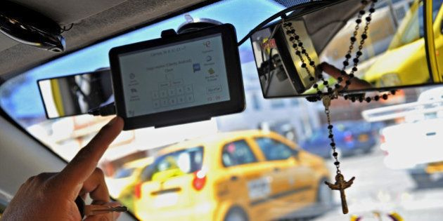 A taxi driver shows an application for smart mobile phones or tablets to order a 'safe taxi' ---wich in connected via GPS---- and able to report dangerous situations through the 'guardian angel' or 'panic button', in Bogota, Colombia, on July 3, 2013. A working group was created by authorities to find solutions for insecurity ---in both taxi drivers and passengers--- following the death of DEA's agent James Terry Watson, who was stabbed in a taxi in Bogota three weeks ago.  AFP PHOTO/Guillermo LEGARIA        (Photo credit should read GUILLERMO LEGARIA/AFP/Getty Images)