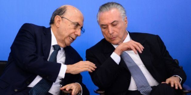 Brazilian Finance Minister Henrique Meirelles (L) and acting President Michel Temer attend a meeting...