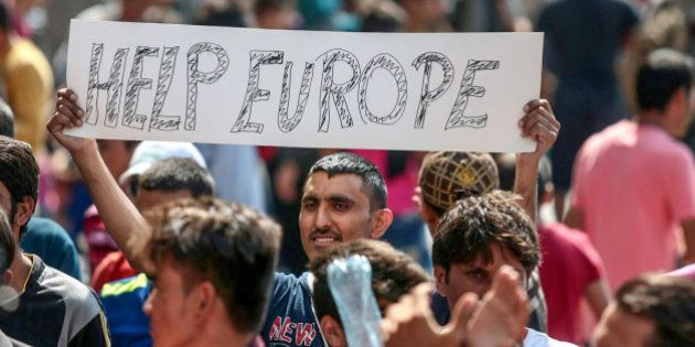A man holds a placard as Syrian and Afghan refugees demand to travel to Germany on 2 September 2015 in...