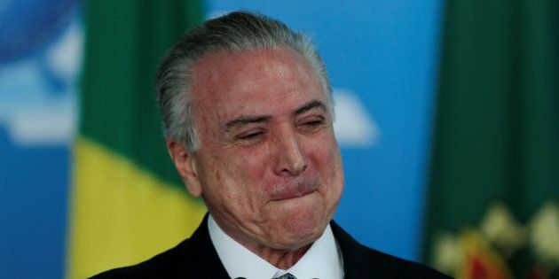 Brazil's interim President Michel Temer smiles during a meeting with business leaders at the Planalto...