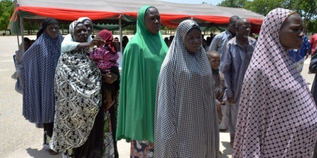 Women, part of the group of 128 detainees released by the Nigerian army, sit in Maiduguri, Borno State,...